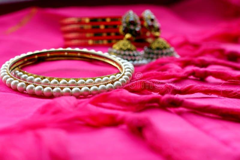 Bracelets et boucles d'oreille ethniques indiens de bijoux sur le tissu rose photos libres de droits
