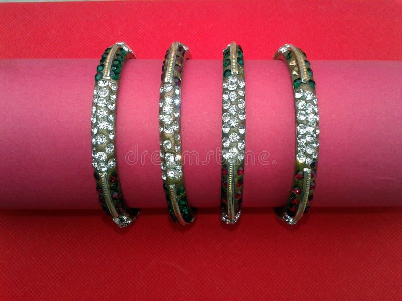 Bracelets indiens avec des combinaisons de couleur uniques sur le fond rouge photographie stock