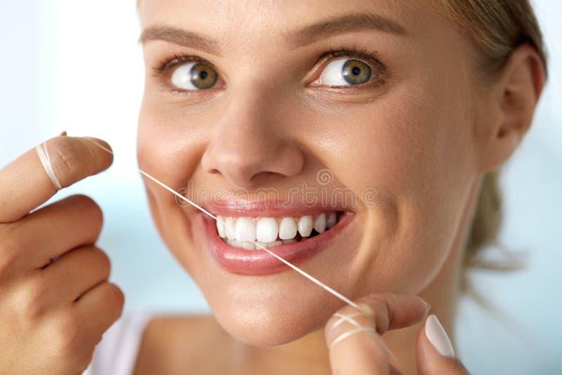 Braces på en vit bakgrund Kvinna med härligt leende genom att använda Floss för tänder royaltyfri fotografi