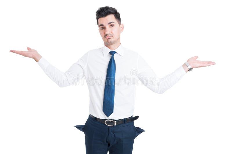 Brach den Verkäufer, der leere Hosentaschen zeigt lizenzfreie stockbilder