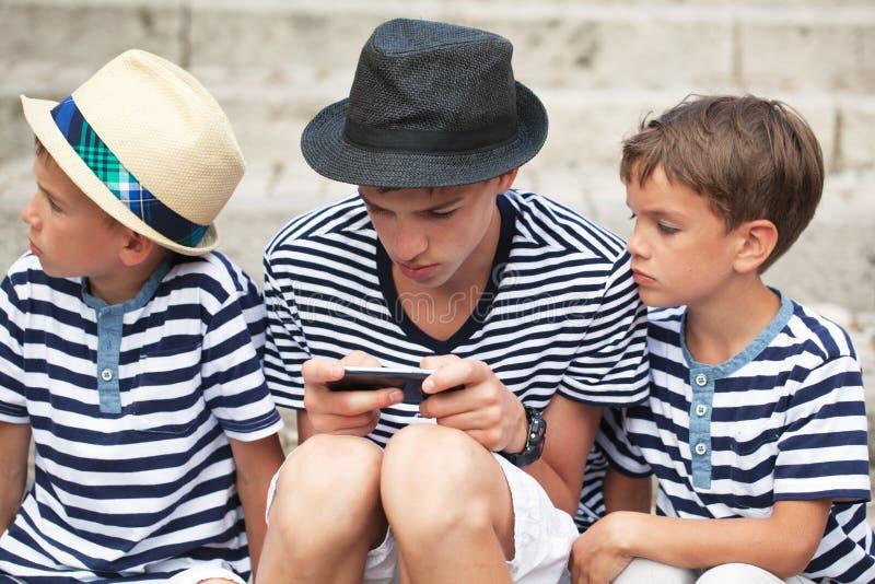 Bracia bawić się grę na twój telefonie obraz royalty free