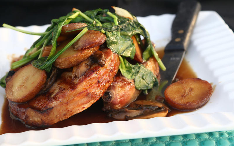 Braciole di maiale con gli spinaci e le patate del sugo del fungo sul piatto bianco fotografia stock libera da diritti
