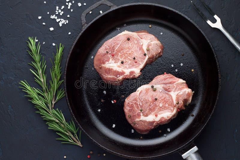 Braciole di maiale crude sulla pentola pronta alla frittura sul fondo di pietra rustico immagine stock