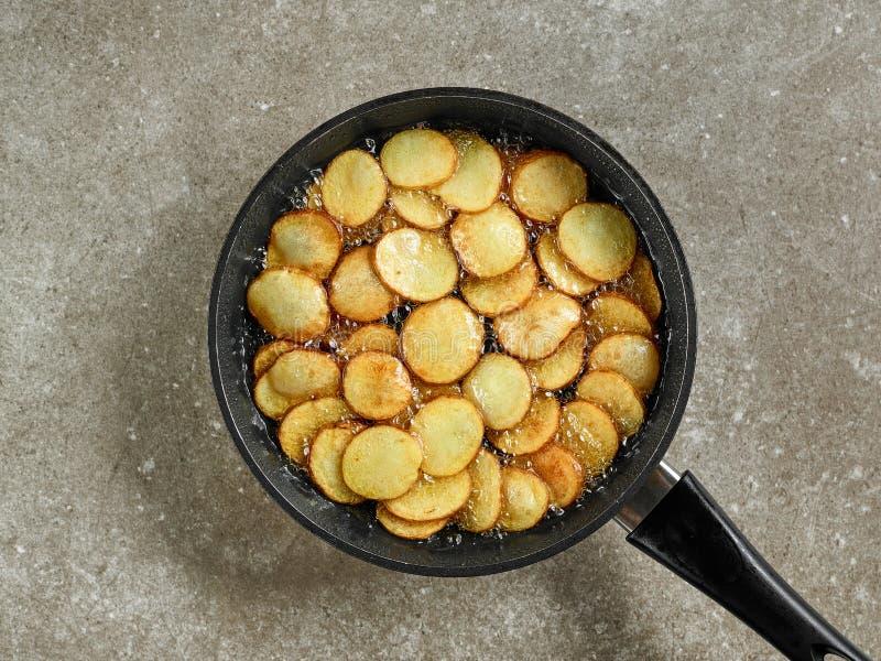Bradende aardappels in een pan stock foto's