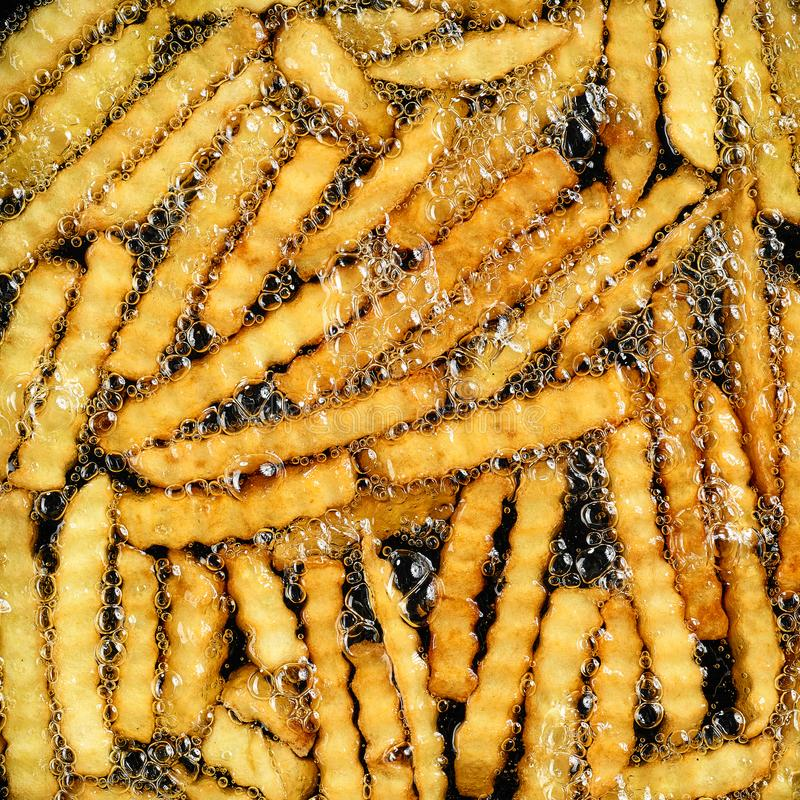 Bradende aardappels in hete olie stock foto