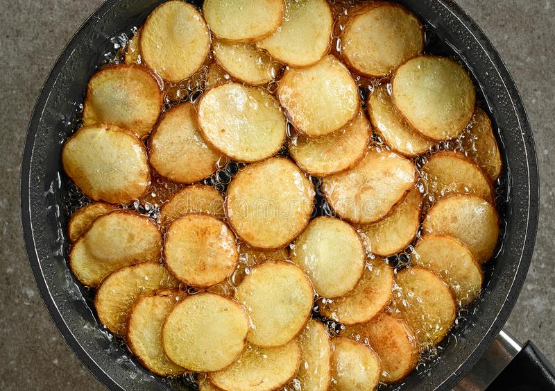 Bradende aardappels in pan met olie stock afbeelding
