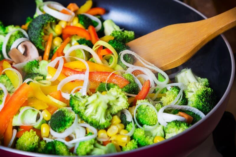 Bradende groenten in pan met spatel royalty-vrije stock afbeeldingen