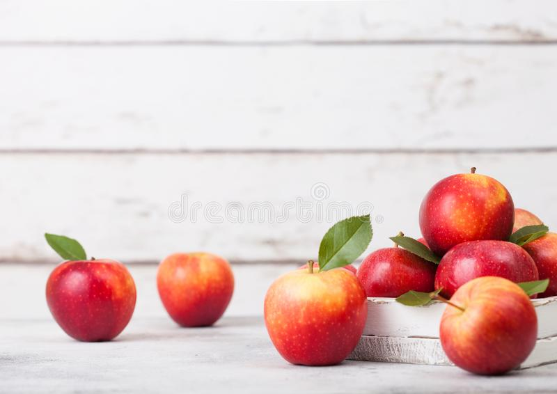 Braeburn pink lady apples in wooden box on white wooden background royalty free stock image