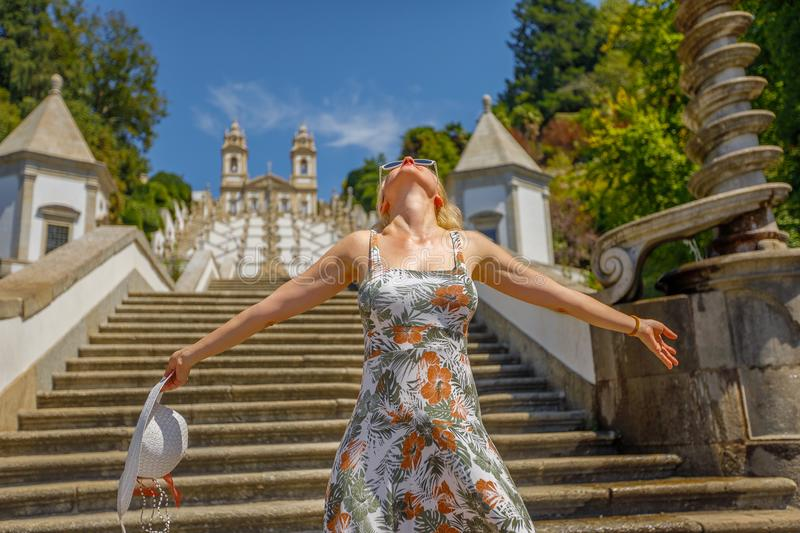 Braga Portugal woman. Freedom caucasian woman with open arms on stairway of Bom Jesus do Monte Sanctuary. Female tourist enjoys at popular landmark and royalty free stock image