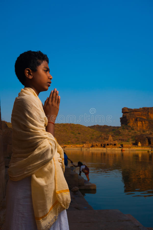 Brahmin Boy Priest Leading Puja Badami Temple. BADAMI, INDIA - February 23, 2009: A young boy Brahmin priest leads a small group prayer at the reservoir edge royalty free stock image