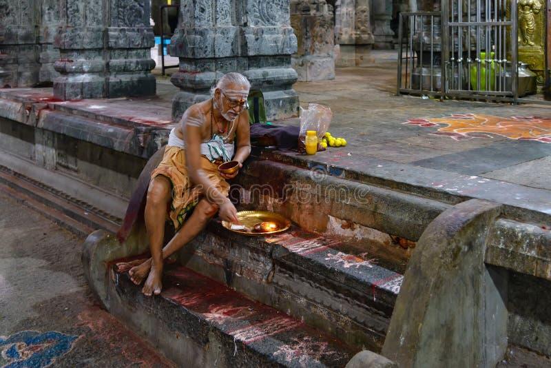 Brahmin in Ekambareswarar Temple, India. Kanchipuram, India - August 19, 2018: A brahmin sitted on steps perform an hindu ritual inside the Ekambareswarar temple stock photo