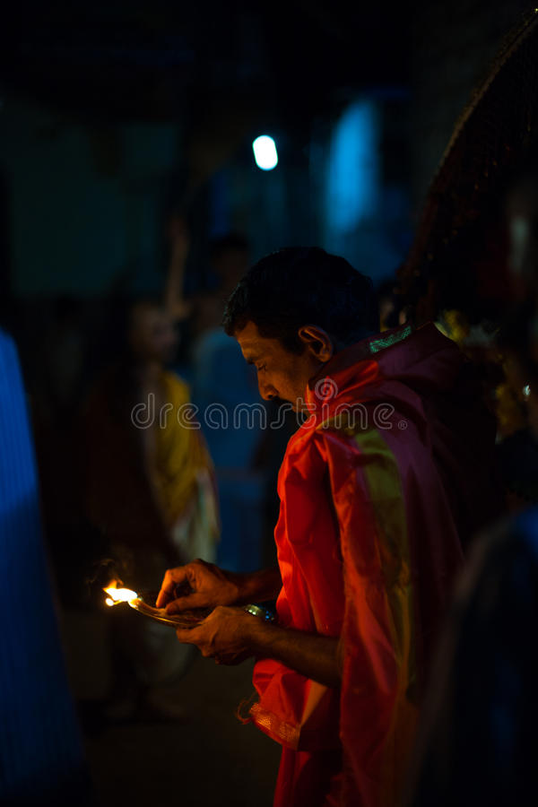 Brahmin Indian Priest Burning Incense Night. GOKARNA, INDIA - MARCH 26, 2009: Unidentified Indian brahmin blesses a residence by burning incense at night during royalty free stock photo