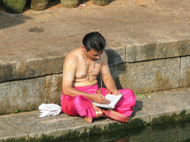 Brahmin Praying. UDUPI, INDIA - Dec 7th - A South Indian brahmin silently chants mantras on the steps of a sacred pond in Udupi, South India on December 7th 2008 royalty free stock photo