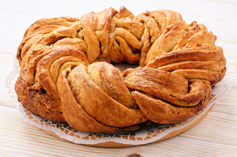 Braided cinnamon roll cake on wooden background. royalty free stock images