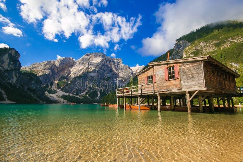 Braies湖与木在背景的小屋的Pragser Wildsee美妙的夏天风景在岸和五颜六色的树和山 免版税图库摄影