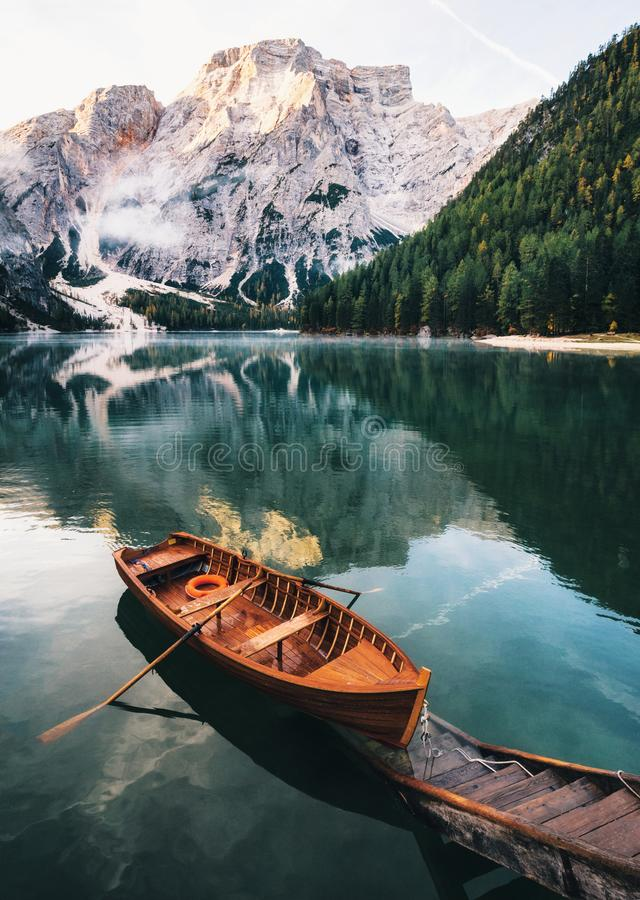Braies lake in Dolomites, Italy. Boats and slip construction in Braies lake with crystal water in background of Seekofel mountain in Dolomites in morning, Italy stock photo