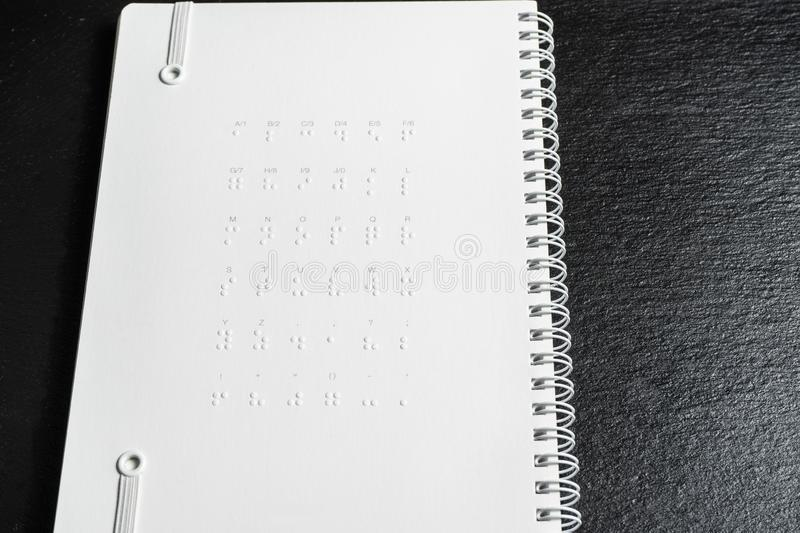 Braille dots - reading without seeing.braille alphabet at the back of notebook.  stock image