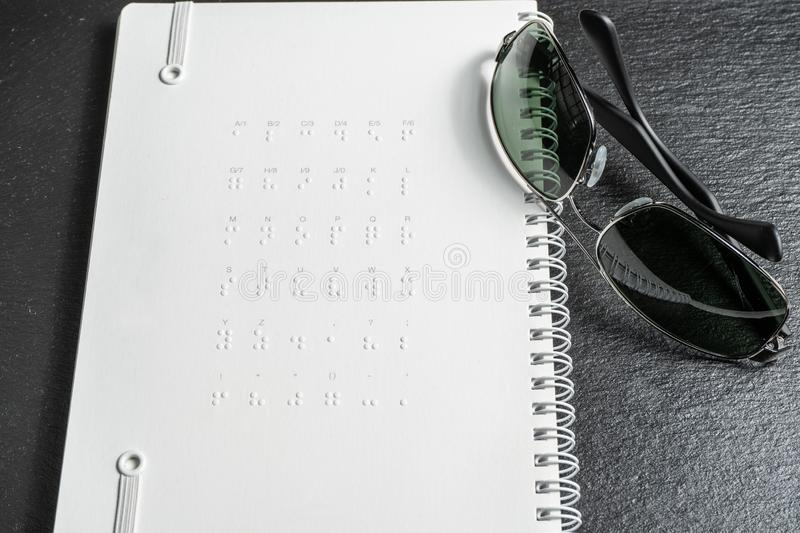 Braille dots - reading without seeing.braille alphabet at the back of notebook.  stock photo