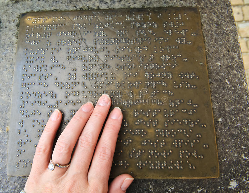 Braille. A hand reading in Braille from a metal plaque with information of landmark at old square in Europe stock photos