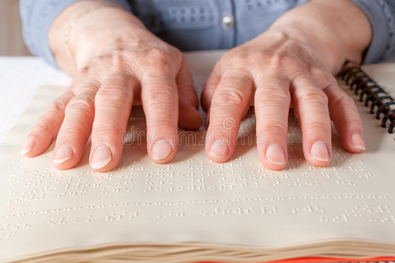 Braille language. Blind old woman reading text in braille language royalty free stock photo