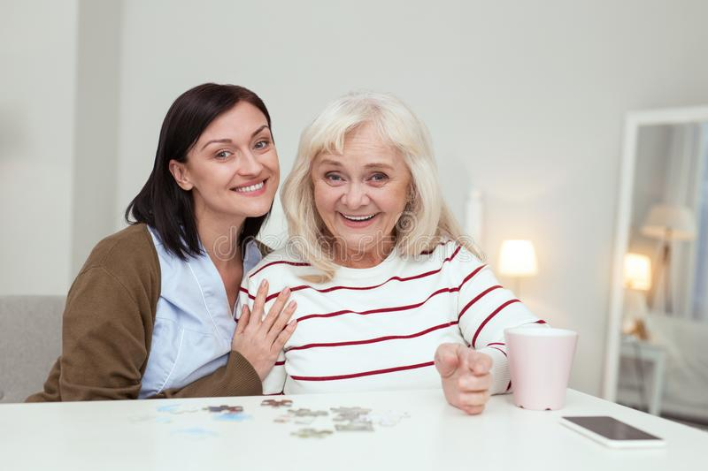 Energetic elder woman and caregiver picking up puzzle. Brain activity. Enthusiastic elder woman and caregiver looking at camera while gathering puzzle stock images