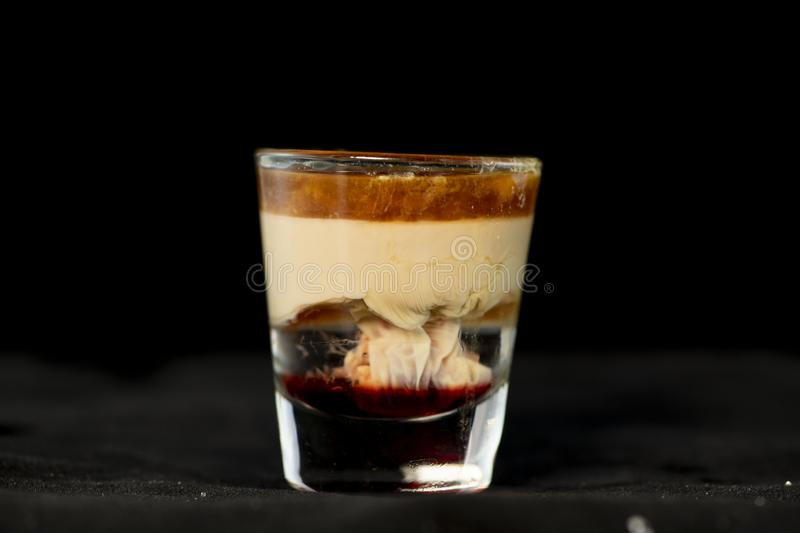 Brain Hemorrhage shot cocktail with schnapps, baileys irish cream and grenadine. With isolated black background royalty free stock photo