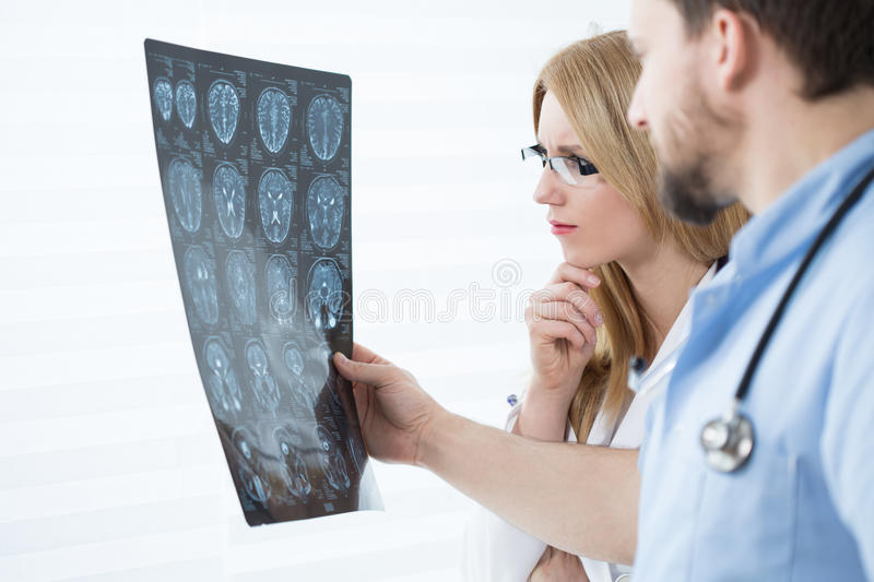 Brain scanning results. Two young experienced doctors looking at brain scanning results royalty free stock photos