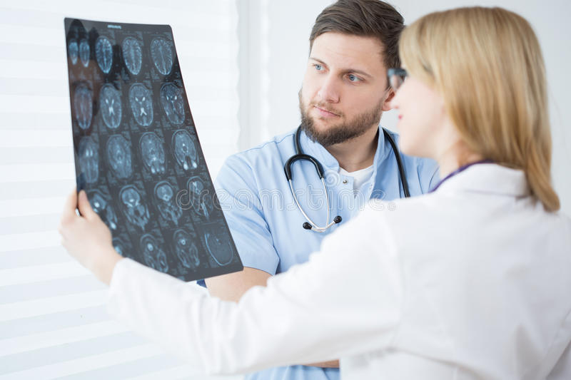 Brain scanning. Two young doctors looking at patient's brain scanning stock photos