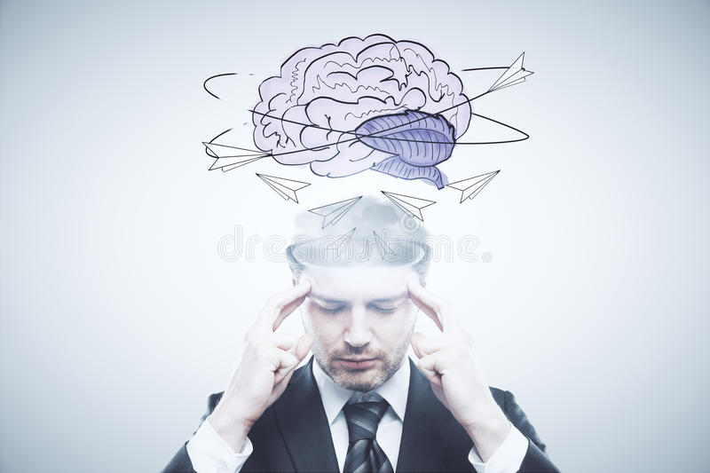 Brain storm concept. Pensive businessman with abstract brain sketch on light background. Brain storm concept stock image
