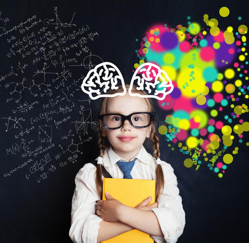 Brain storming and creativity education concept. Smiling little girl on blackboard background with science and art pattern royalty free stock photos