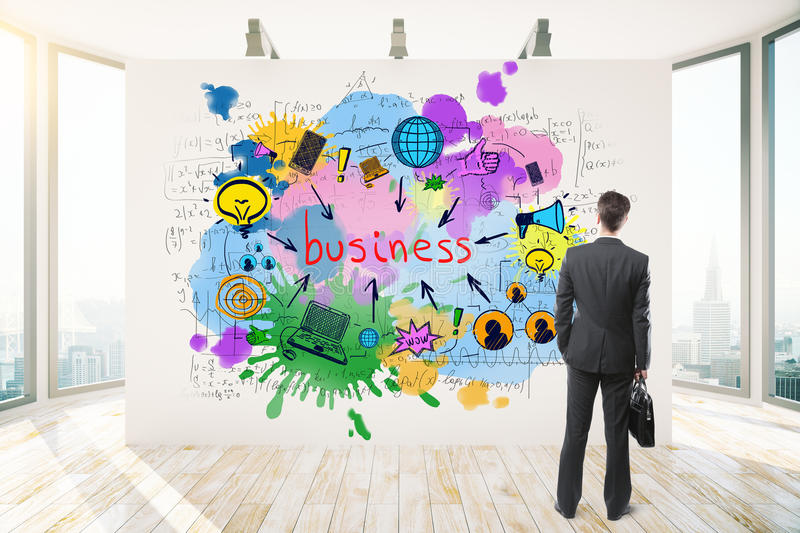 Brainstorm concept. Back view of thoughtful businessman looking at whiteboard with business sketch in modern interior with city view and daylight. Brainstorm royalty free stock photo