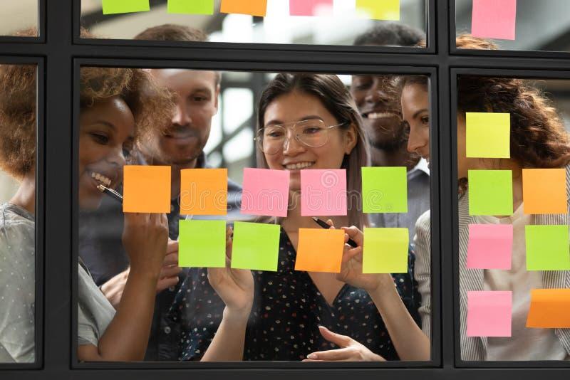 Brainstorm de colegas multiétnicos sonrientes usando stickers para publicar imagen de archivo