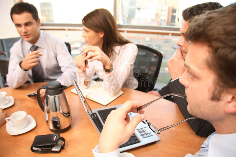 Brainstorm - four people. Group of business people sitting at the table, working on project - two men and two women stock photo