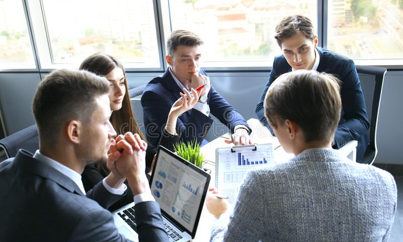 Brainstorm. Group of business people looking at the laptop together. One business woman looking at camera. royalty free stock photos