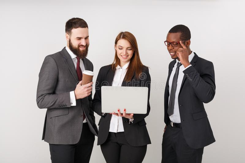 Business people looking at laptop and smiling stock photo