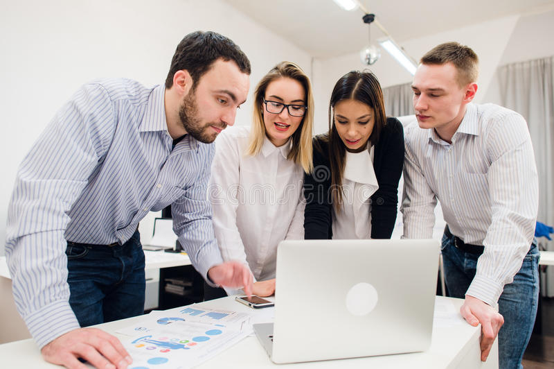 brainstorm Groupe de gens d'affaires gais dans la tenue de détente futée regardant l'ordinateur portable ensemble et le sourire image stock