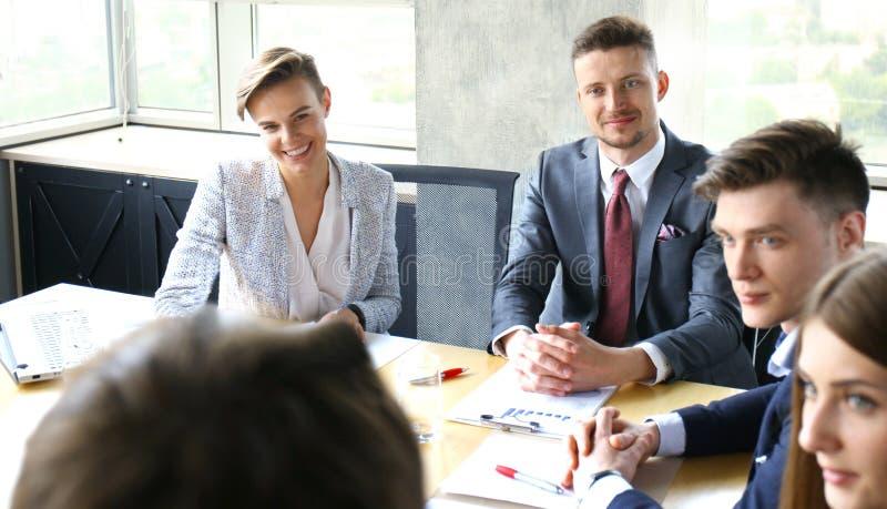 brainstorm Grupo de executivos que olham o portátil junto Uma mulher de negócio que olha a câmera imagens de stock