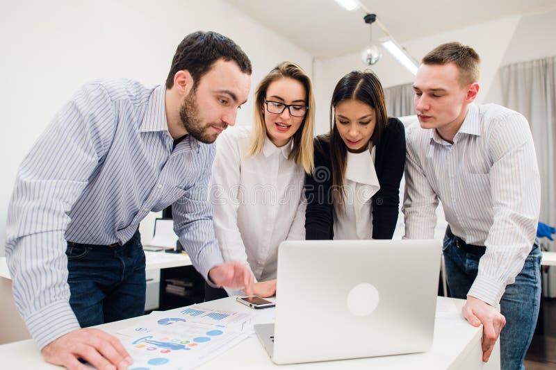 brainstorm Gruppo di gente di affari allegra nell'abbigliamento casual astuto che esamina insieme il computer portatile e sorride immagine stock