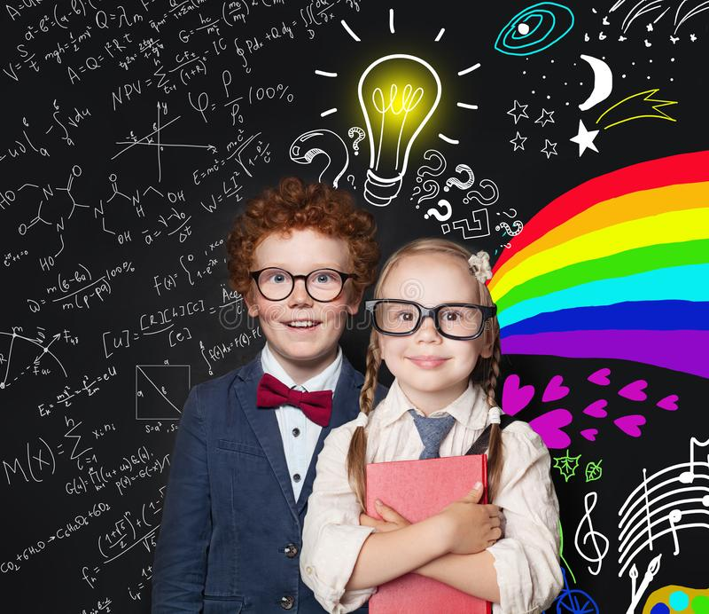 Brainstorm, idea and creativity concept. Happy smart kids in glasses on blackboard background with light bulb, science formulas royalty free stock photo