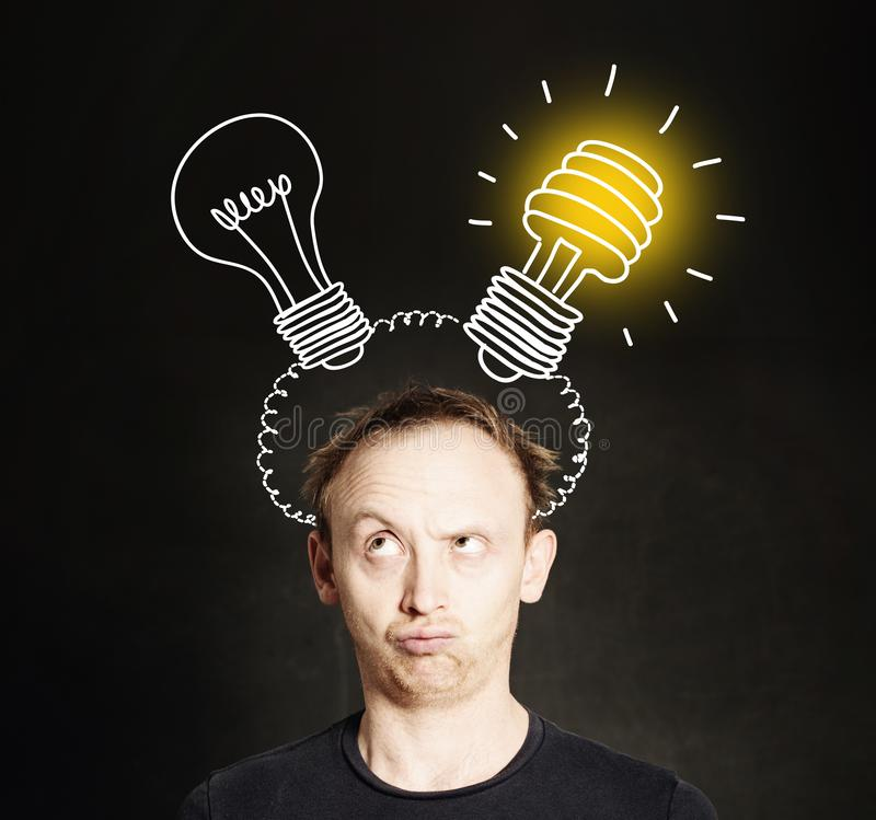 Brainstorm. Man with two light bulb on blackboard background. Brainstorming and idea concept royalty free stock photography