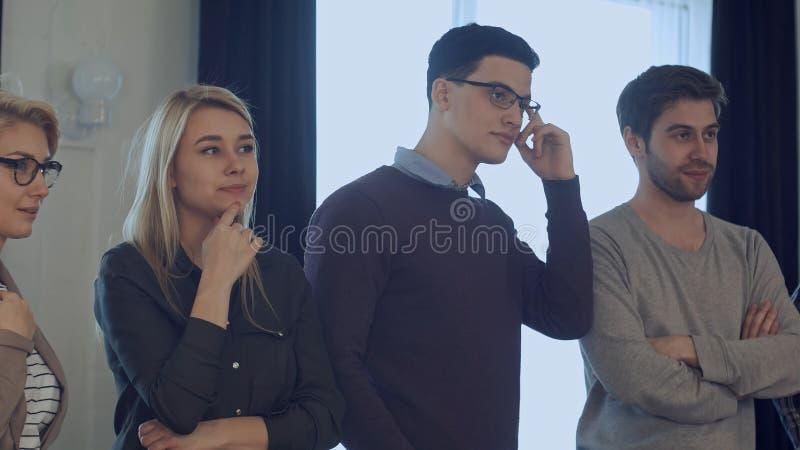 'brainstorming' ακροατηρίων, συνάδελφοι που στέκεται και που ακούει ένα λεωφορείο στοκ εικόνα