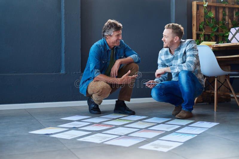 'brainstorming' δύο συναδέλφων χαμόγελου με τα έγγραφα για ένα πάτωμα γραφείων στοκ φωτογραφία με δικαίωμα ελεύθερης χρήσης