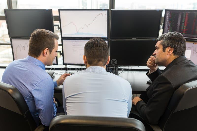 'brainstorming' επιχειρησιακών ομάδων ελέγχοντας τα στοιχεία στις οθόνες υπολογιστή στοκ φωτογραφίες με δικαίωμα ελεύθερης χρήσης