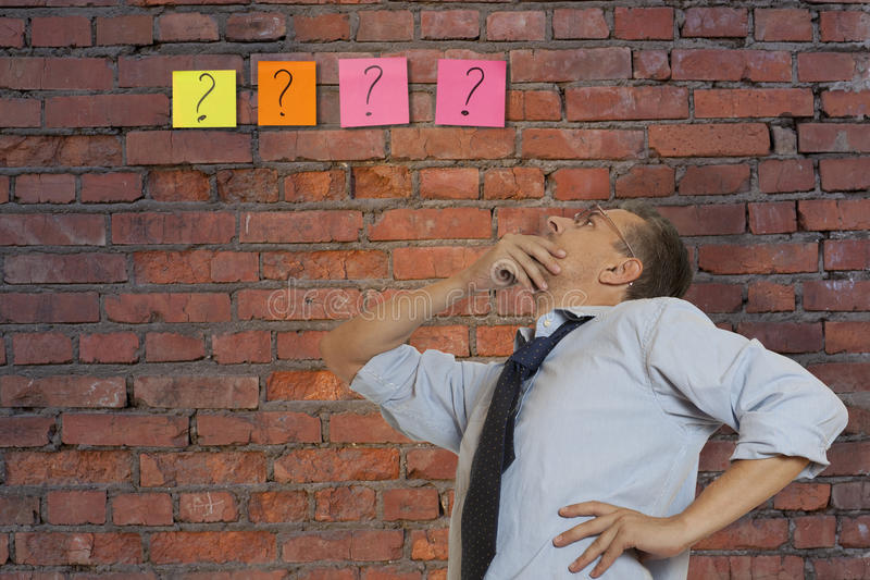 Brainstorming. The man costs opposite to a brick wall stock photography