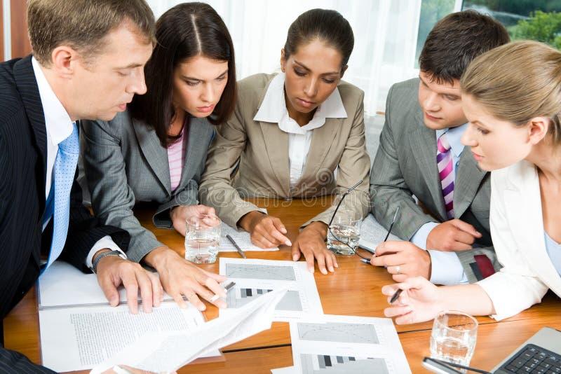 Brainstorming. Image of five people looking at business-plan and brainstorming