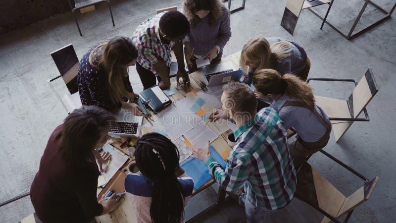 Brainstorming als creatieve gemengde rasgroep mensen op modern kantoor Hoogste mening van groep mensen die zich dichtbij lijst be royalty-vrije stock afbeelding