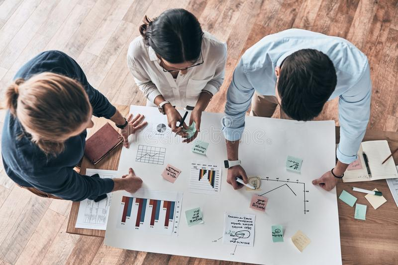 Brainstorming. Close up top view of young confident business people working together while man writing on blueprint in the office royalty free stock photo