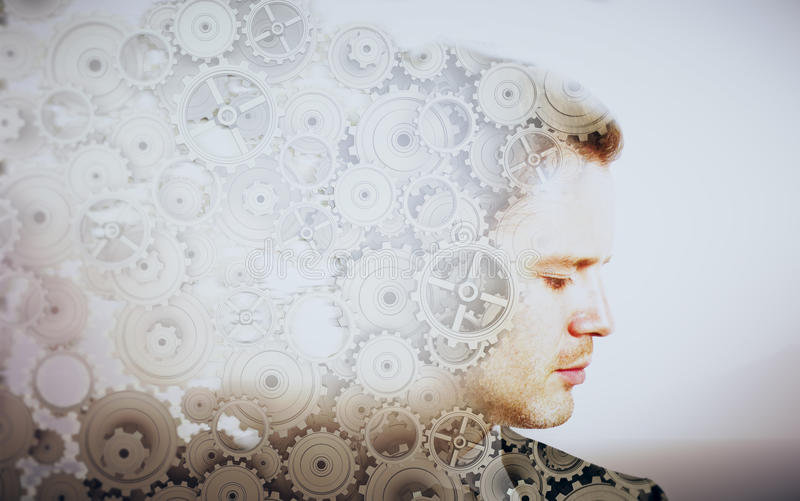 Brainstorming concept. Side portrait of young businessman with cogwheels on light background. Brainstorming concept. Double exposure stock images