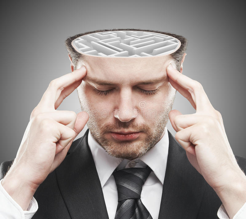 Brainstorming concept. Thoughtful young businessman with abstract concrete maze inside head. Brainstorming concept royalty free stock photo