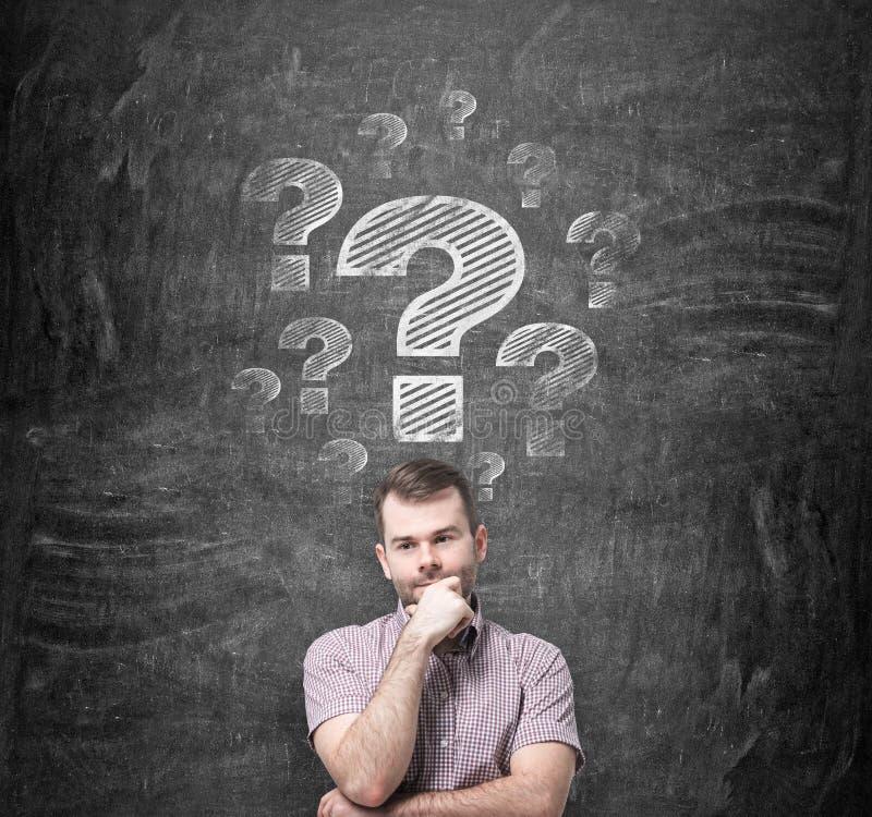 Brainstorming des Mannes Fragezeichen werden auf die schwarze Tafel hinter die Person gezeichnet stockbild